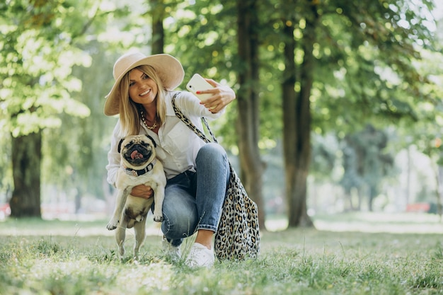 Vrouw met een wandeling in het park met haar pug-hond huisdier Gratis Foto