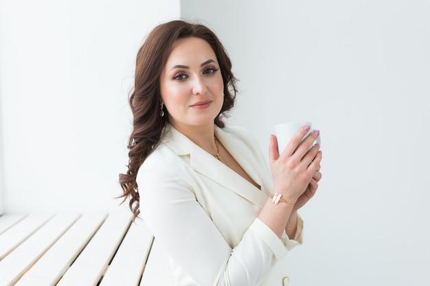Vrouw met een witte kop koffie. met een mooie manicure. drinken, mode, morgen Premium Foto