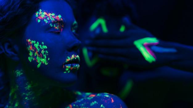 Vrouw met fluorescerende make-up op gezicht en hand Gratis Foto