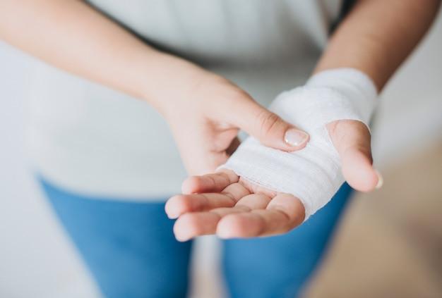 Vrouw met gaasverband gewikkeld om haar hand Gratis Foto