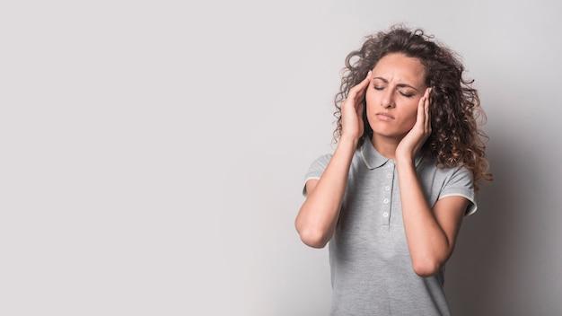 Vrouw met gesloten ogen die aan hoofdpijn tegen grijze achtergrond lijden Gratis Foto