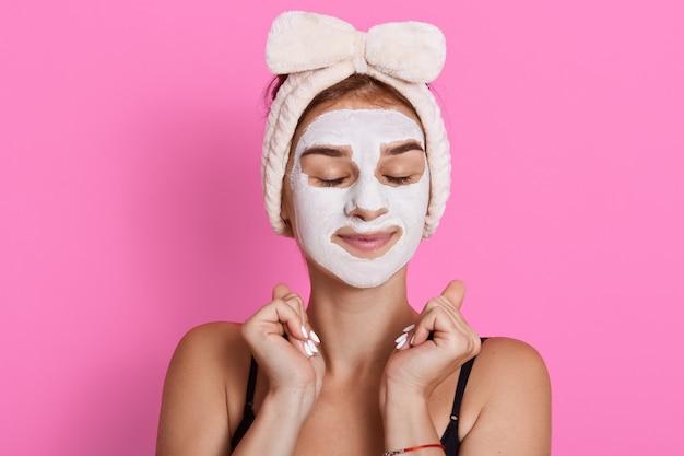 Vrouw met gesloten ogen en wit gezichtsmasker op gezicht, die mouwloos t-shirt en haarband draagt Gratis Foto