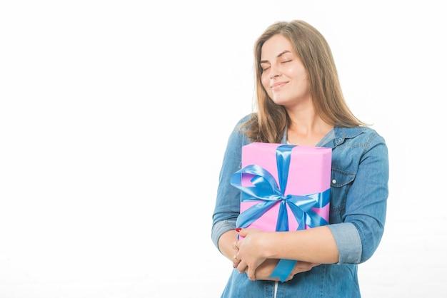 Vrouw met gesloten ogen het houden van verjaardagsgift op witte achtergrond Gratis Foto