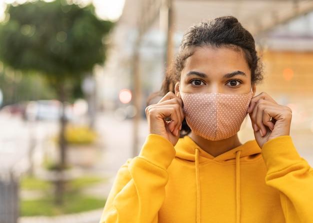 Vrouw met gezichtsmasker en sociaal afstandsconcept Gratis Foto