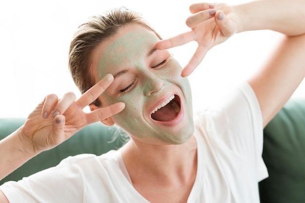 Vrouw met gezichtsmasker en vredestekensgebaar Gratis Foto