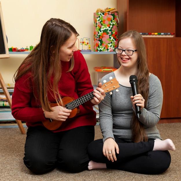 Vrouw met gitaar en meisje met het syndroom van down plezier Premium Foto
