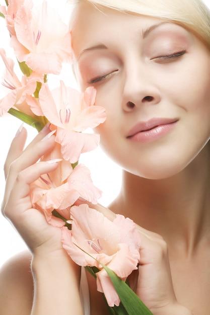 Vrouw met gladiolenbloemen in haar handen Premium Foto