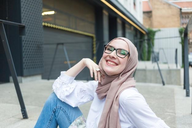 Vrouw met glazen en hijab het glimlachen Gratis Foto