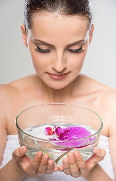 Vrouw met glazen kom met water en orchideebloemen. Premium Foto