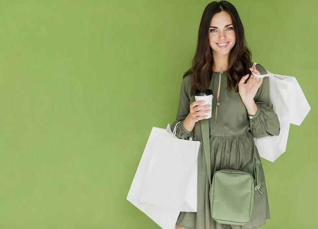 Vrouw met groene handtas en koffie op groene achtergrond Premium Foto