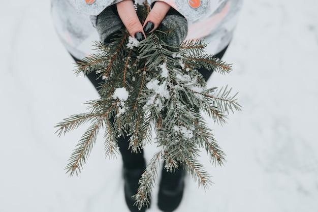 Vrouw met groene pijnboomtakken met sneeuw op onscherpe achtergrond Gratis Foto