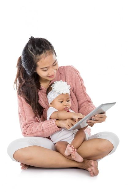 Vrouw met haar baby die tablet samen gebruiken Premium Foto