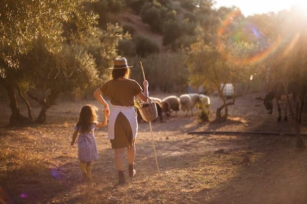 Vrouw met haar dochter die schapen op het gebied hoeden Gratis Foto
