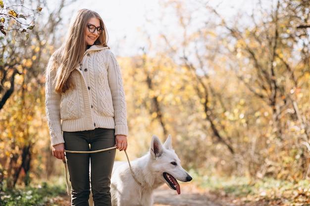 Vrouw met haar hond die in park loopt Gratis Foto