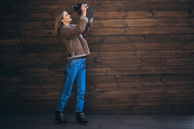 Vrouw met haar huisdieren franse buldog op houten achtergrond Gratis Foto