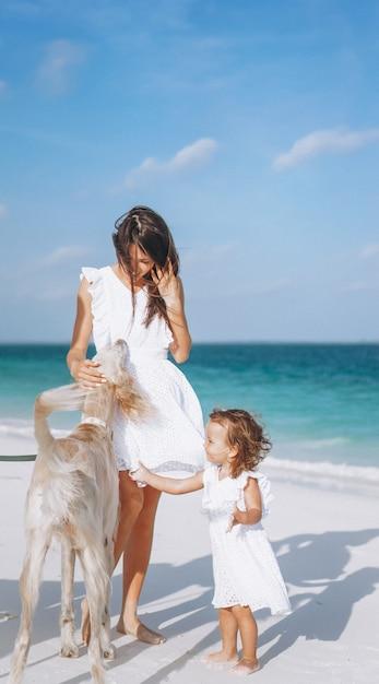 Vrouw met haar kleine dochter die met honden bij het strand door de oceaan speelt Gratis Foto