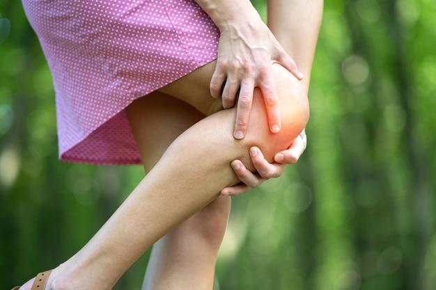 Vrouw met haar knie met handen met sterke pijn. Premium Foto