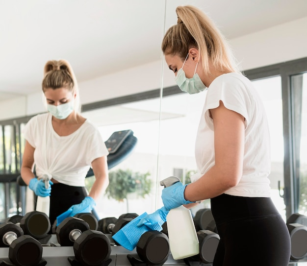 Vrouw met handschoenen en medisch masker gewichten desinfecteren in de sportschool Gratis Foto