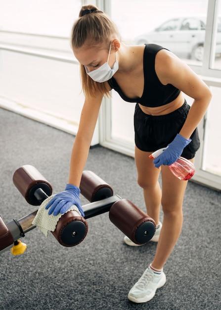 Vrouw met handschoenen en medisch masker op de desinfecterende uitrusting van de sportschool Gratis Foto