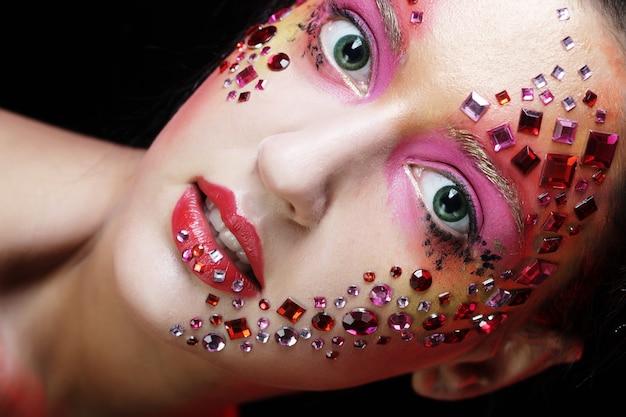 Vrouw met heldere artistieke make-up Premium Foto