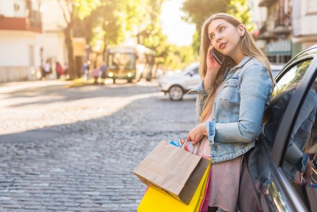 Vrouw met heldere boodschappentassen praten via de telefoon in de straat Gratis Foto