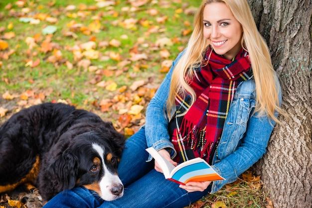Vrouw met het boek van de hondlezing in de herfstpark Premium Foto