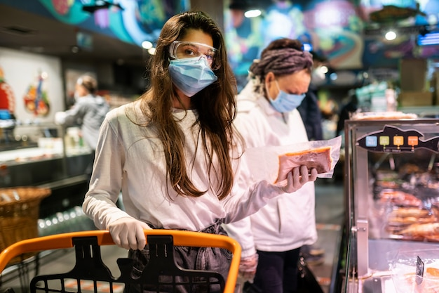 Vrouw met het chirurgische masker en de handschoenen is winkelen in de supermarkt Gratis Foto