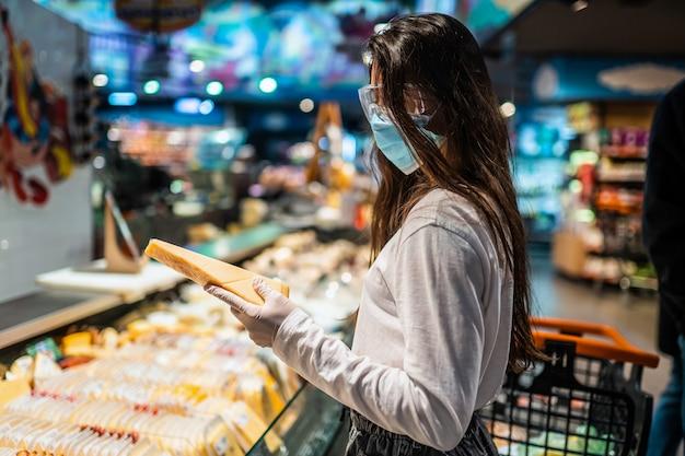 Vrouw met het chirurgische masker en de handschoenen winkelt in de supermarkt na een coronavirus-pandemie. het meisje met chirurgisch masker gaat kaas kopen. Gratis Foto