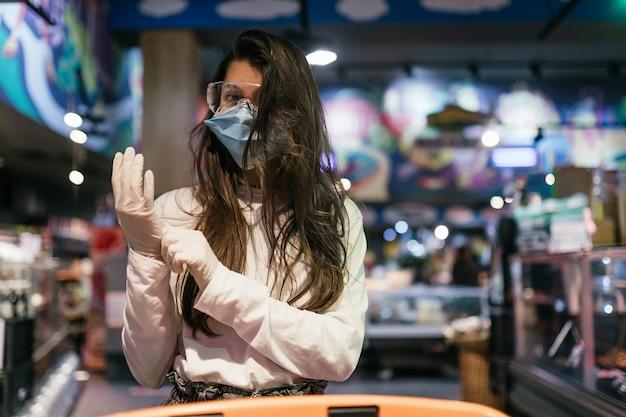 Vrouw met het chirurgische masker en de handschoenen winkelt in de supermarkt Gratis Foto