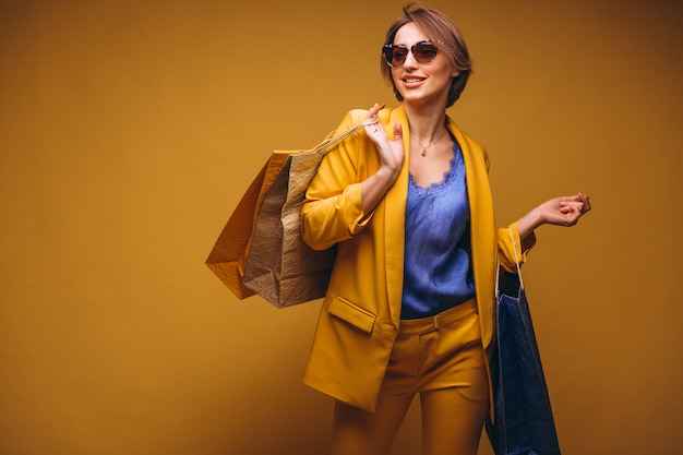 Vrouw met het winkelen zakken in studio op gele geïsoleerde achtergrond Gratis Foto