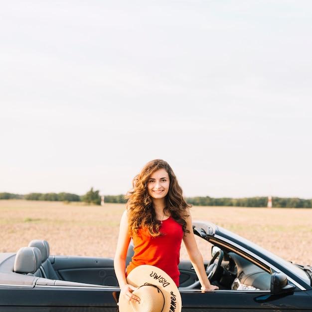 Vrouw met hoed dichtbij auto Gratis Foto