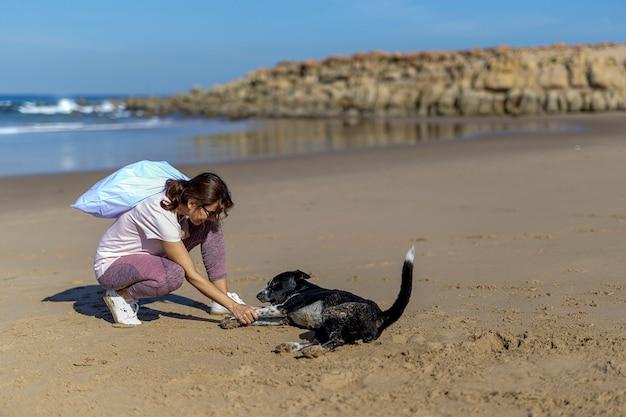 Vrouw met hond die afval opneemt en plastieken die het strand schoonmaken Premium Foto