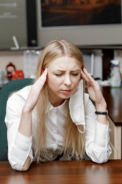 Vrouw met hoofdpijn op kantoor, ziek op het werk voelen Premium Foto