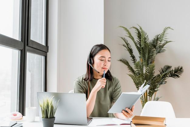 Vrouw met hoofdtelefoon die videogesprek op laptop heeft Gratis Foto