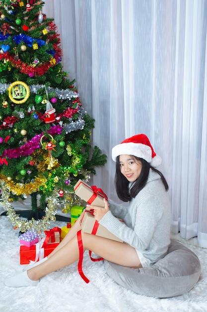 Vrouw met kerstmuts blij met kerstcadeau Gratis Foto