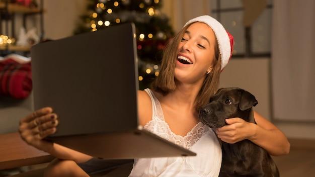 Vrouw met kerstmuts met haar hond aan mensen op afroep met behulp van laptop Gratis Foto