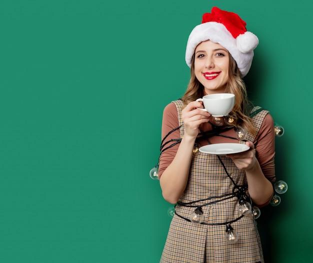 Vrouw met kerstverlichting en kopje koffie op groene muur Premium Foto