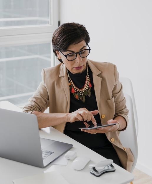 Vrouw met ketting wat betreft een tablet Gratis Foto