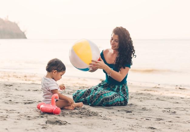 Vrouw met kind op strand Gratis Foto