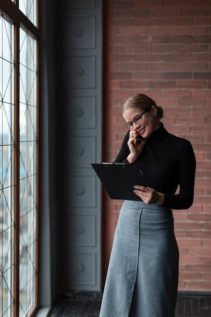 Vrouw met klembord dat over telefoon spreekt Gratis Foto