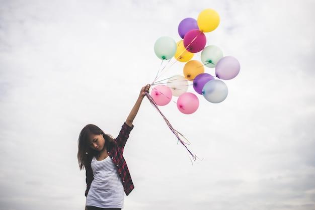 Vrouw met kleurrijke ballonnen buiten blauwe hemel achtergrond. Premium Foto
