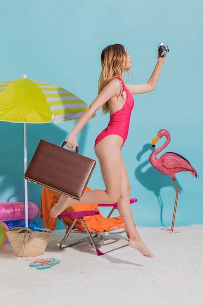 Vrouw met koffer die op strand loopt Gratis Foto