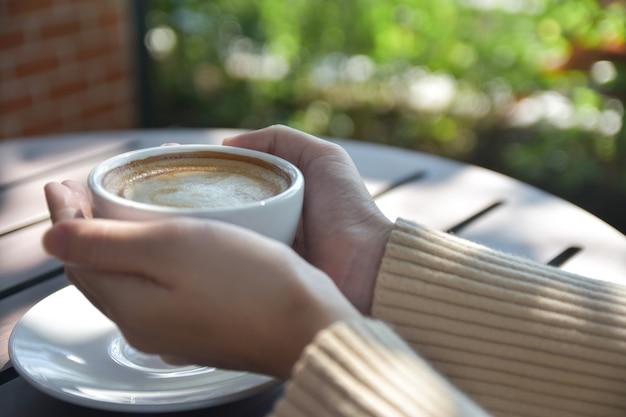 Vrouw met kopje koffie in het café Premium Foto