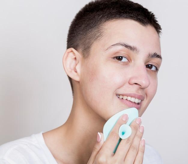 Vrouw met kort haar die haar gezicht schoonmaakt terwijl het bekijken de camera Gratis Foto