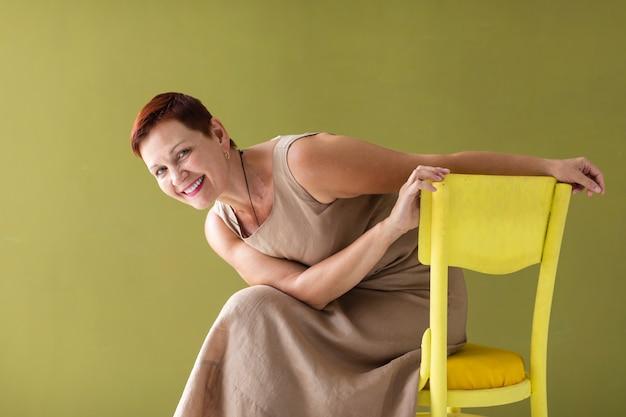 Vrouw met korte haarzitting op stoel Gratis Foto
