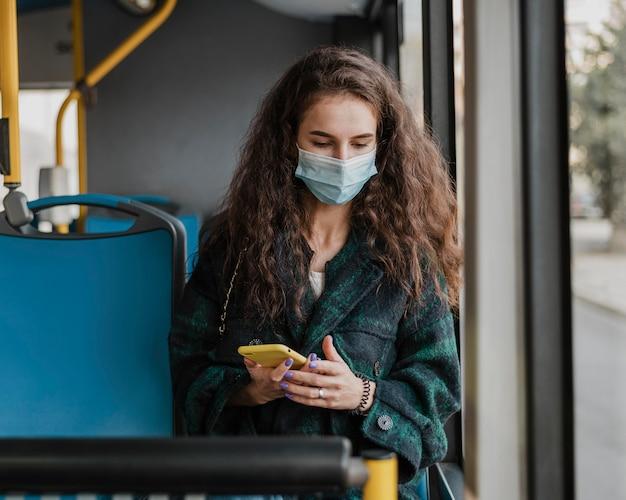 Vrouw met krullend haar die medisch masker vooraanzicht dragen Gratis Foto