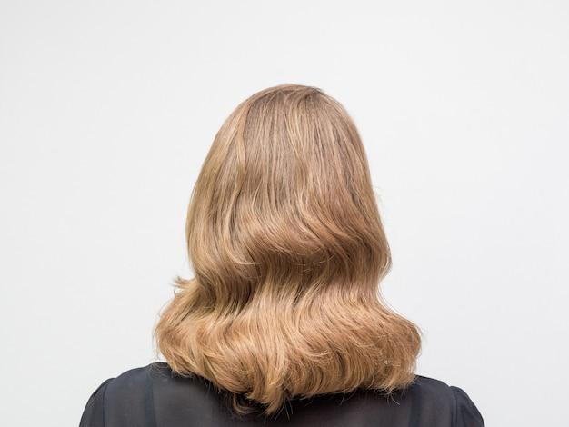Vrouw met lang blond haar en elegant kapsel in retro stijl van golvend haar in een schoonheidssalon. achteraanzicht. Premium Foto