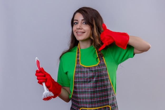 Vrouw met lang golvend haar die een schort en rubberen handschoenen draagt die een schrobborstel houdt en bel me gebaar maakt op zoek naar zelfverzekerd glimlachend vriendelijk Gratis Foto