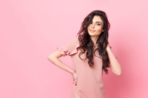 Vrouw met lang krullend haar in een roze jurk. Premium Foto