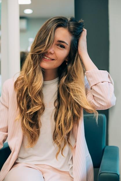 Vrouw met lange haarzitting in een kapper Premium Foto
